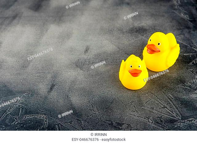 Set of yellow rubber ducks on a black concrete background