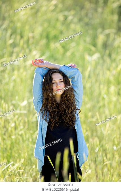 Caucasian woman with arms raised standing in field of tall grass
