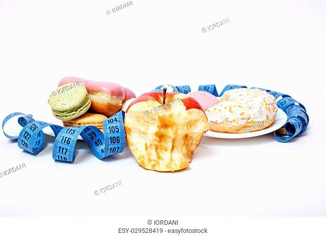 new diet concept, question sign in shape of measurment tape between red apple and donut, cake, macaroon isolated on white, hard choice