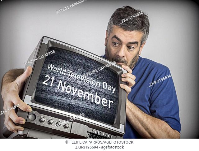 Middle-aged man holds a TV with World Television Day 21 November screen, conceptual image