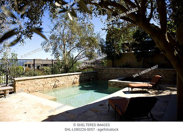 Tuscan style back yard with swimming pool and lounge chairs