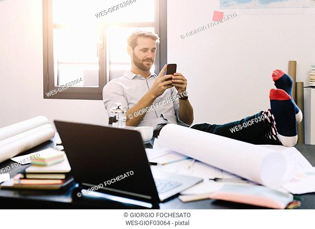 Portrait of smiling architect sitting with feet up at desk using cell phone