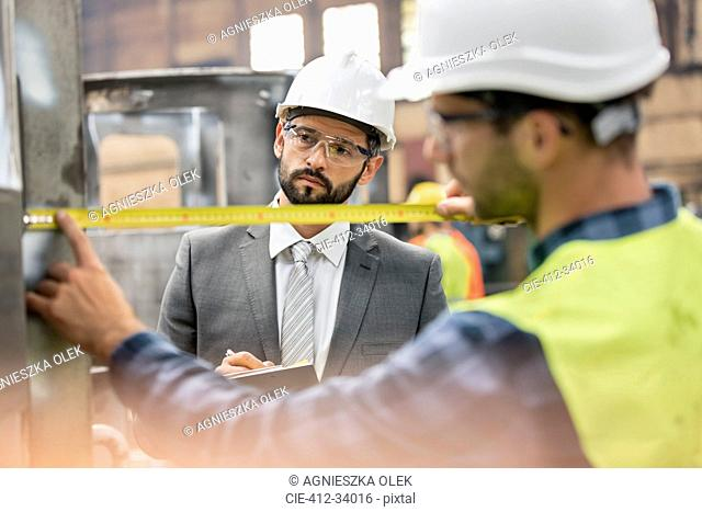 Manager watching steel worker with tape measure in factory
