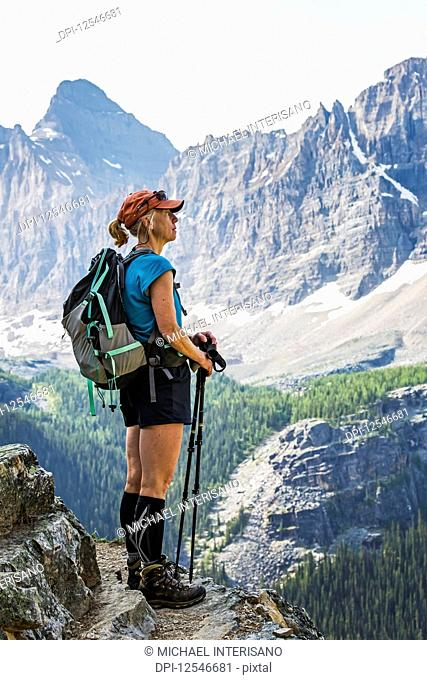 Female hiker standing on cliff edge overlooking mountains and valley; British Columbia, Canada