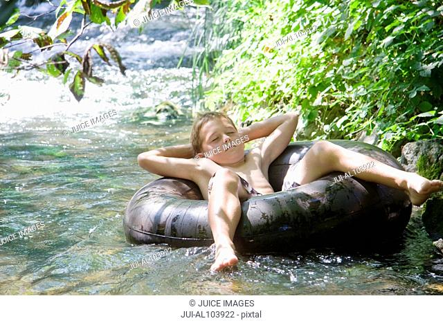 A young boy floating down a river on an inflatable ring with eyes closed, relaxing