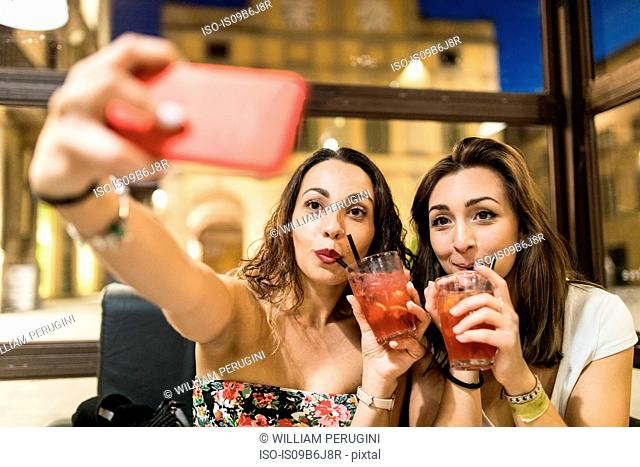 Women drinking cocktails taking selfie with smartphone