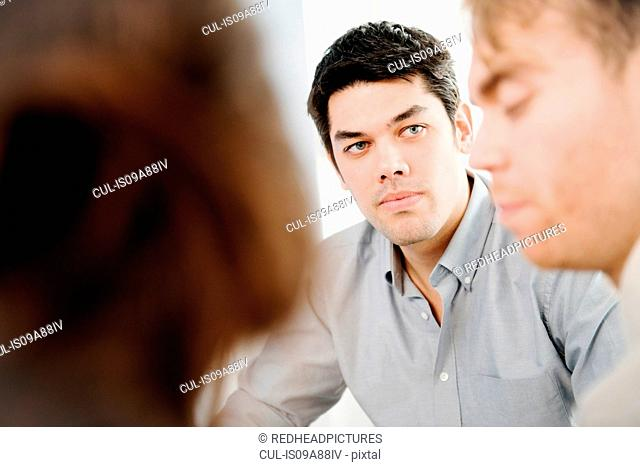 Man wearing shirt looking at male colleague