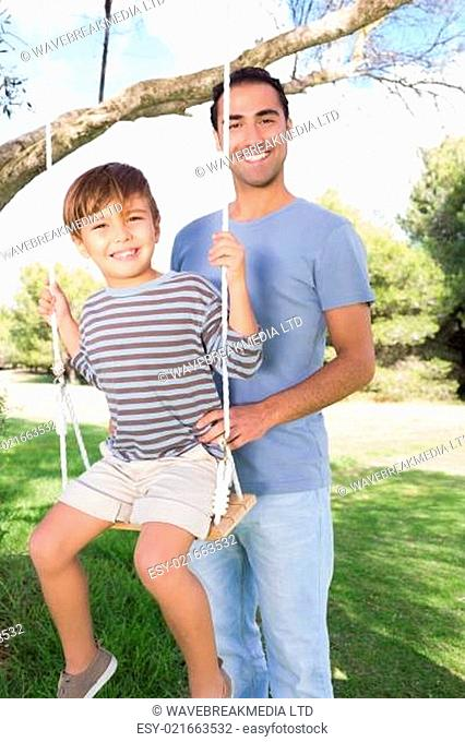Portrait of happy father pushing son on a swing hanging from a tree in the park