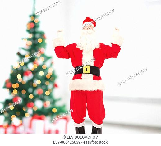 holidays and people concept - man in costume of santa claus having fun over living room and christmas tree background