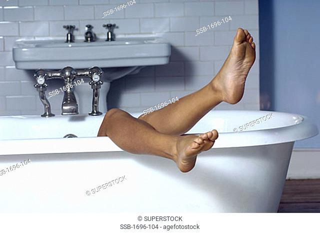 Person's legs on the edge of a bathtub
