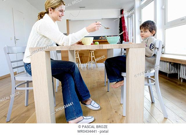 Side profile of a mother feeding her son with a spoon at the dining table