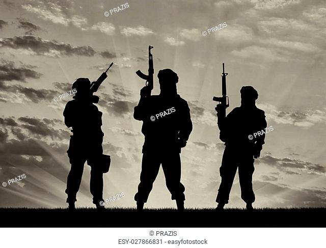 Concept of a terrorist. Silhouette of terrorists with a rifle and a reflection on the water at sunset