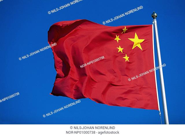 A chinese national flag waving against blue sky