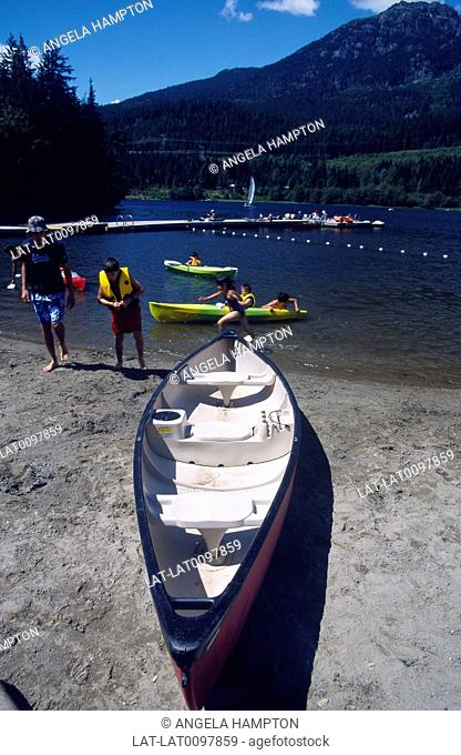 Garibaldi Point. Near Whistler. Boat hire. Canoe on sand. People in lief vests,jackets