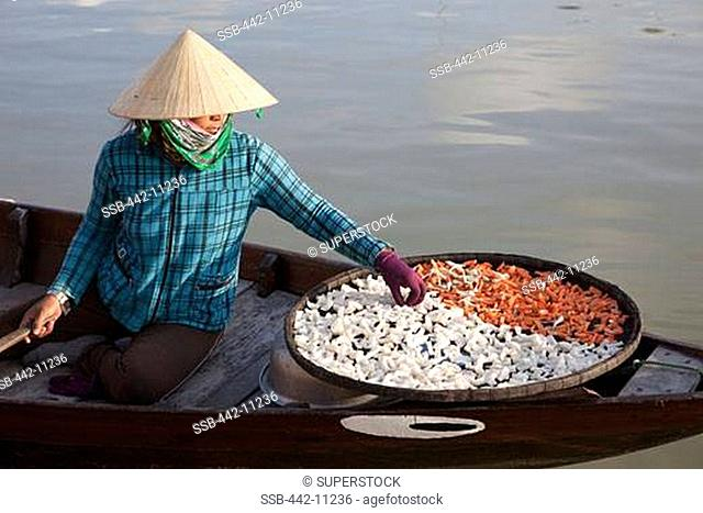 Female vendor selling dried food in a boat, Hoi An, Vietnam