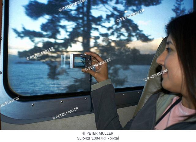 Woman taking pictures at train window