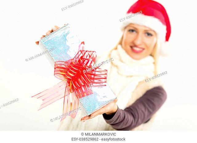 Close-up beautifully wrapped gift with a decorative bow, holding a young pretty blonde girl with Santa's hat. The girl is out of focus