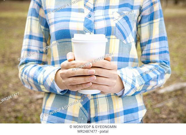 Woman's hands holding a takeout coffee