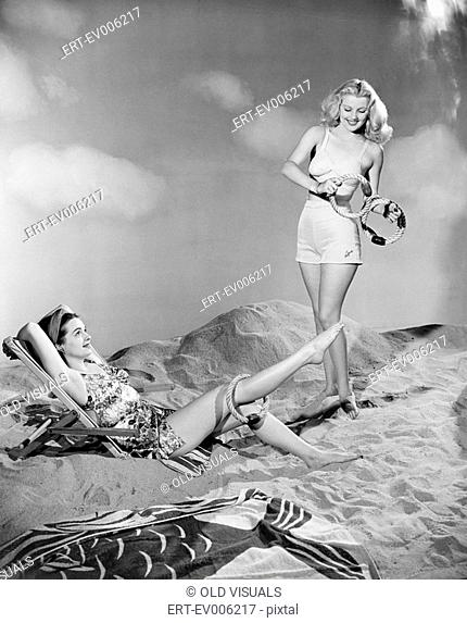 Two women relax at the beach All persons depicted are not longer living and no estate exists Supplier warranties that there will be no model release issues