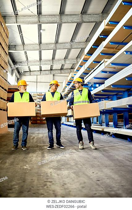 Three workers carrying boxes in factory warehouse