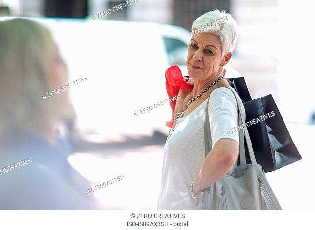 Senior woman posing with shopping bags in city