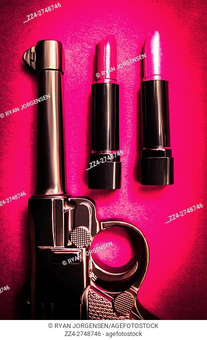 Deadly beauty concept with a gun and pink lipstick makeup bullets. If looks could kill