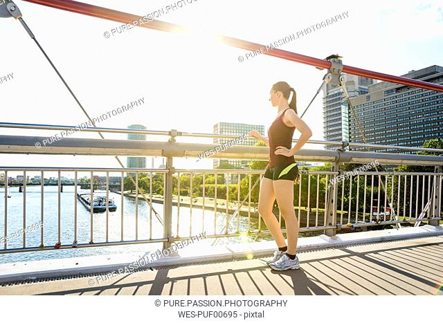 Germany, Frankfurt, sportive young woman standing on bridge