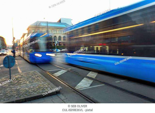 Blue trams passing in opposite directions in city, blurred motion