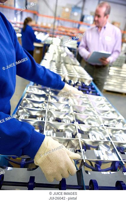 Worker lifting tray of aluminium light fittings in factory