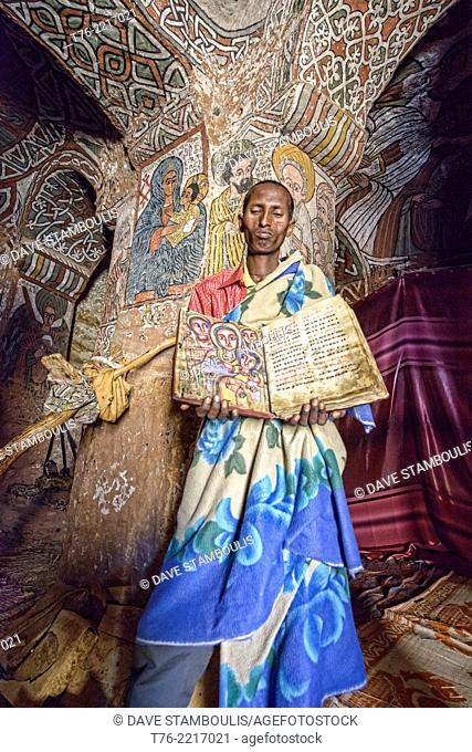 priest reading hundred years old Bible in the Abuna Yemata Guh rock church in Tigray, Ethiopia