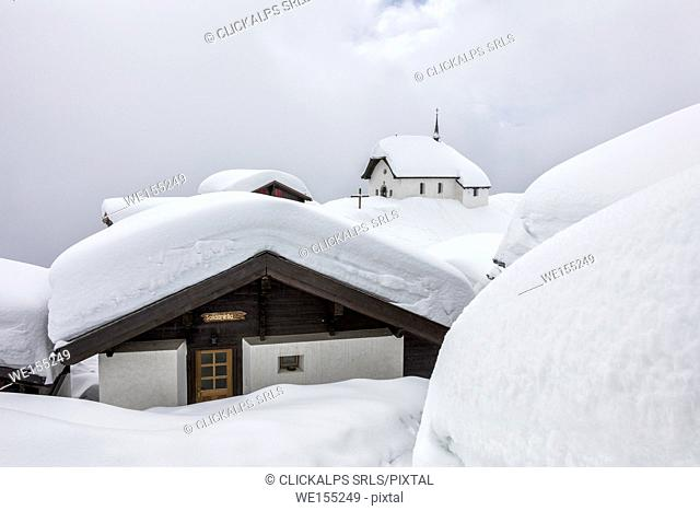 Snow covered mountain huts and church surrounded by low clouds Bettmeralp district of Raron canton of Valais Switzerland Europe