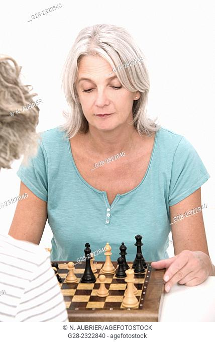 Beautiful mature woman playing chess with another senior woman