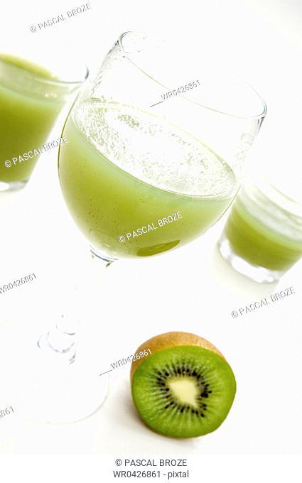 Close-up of three glasses of kiwi juice with a kiwi fruit