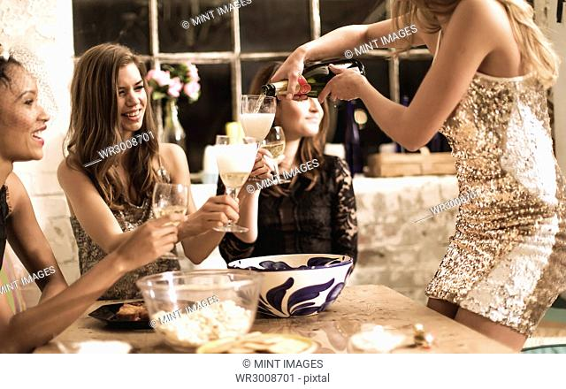 A group of women at a party, pouring and drinking champagne