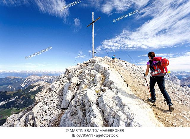 Mountaineer at the summit cross of Mt Heiligkreuzkofel of the Fanes Group in the Fanes-Sennes-Prags Nature Park, Val Badia below, Alta Badia, Dolomites