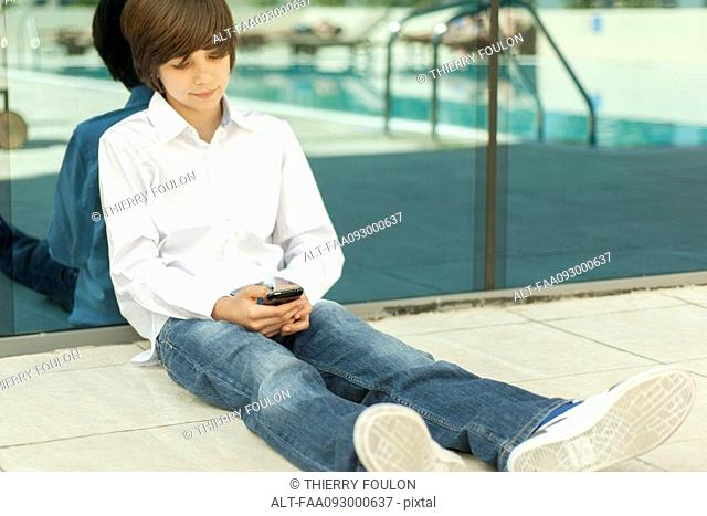Teenage boy sitting on ground using cell phone
