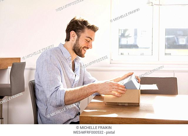 Young man sitting at a table unpacking cardboard box