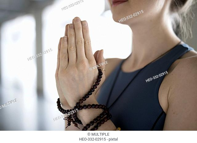 Close up woman with prayer beads practicing yoga meditation with hands at heart center