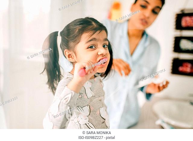 Girl with mother brushing her teeth in bathroom