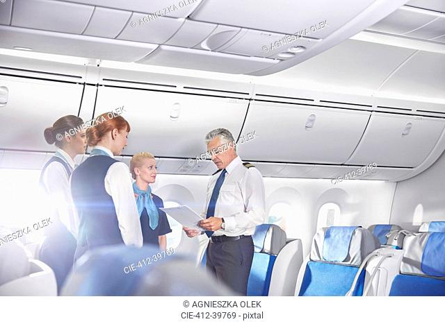 Pilot and flight attendants talking, preparing on airplane