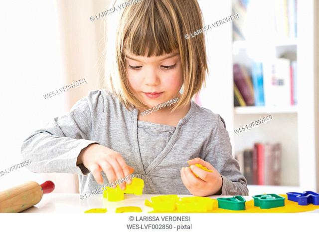 Little girl cutting out yellow modeling clay