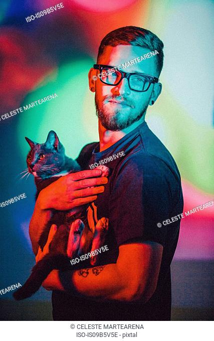 Portrait of young man holding pet cat, against colourful studio background