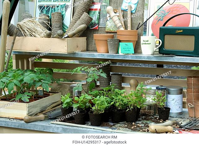 Green Roberts radio and plants in pots with equipment in boxes on shelves in greenhouse. Hartley Botanic Ltd / Chelsea Flower Show 2006