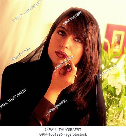 Arab woman applying lipstick
