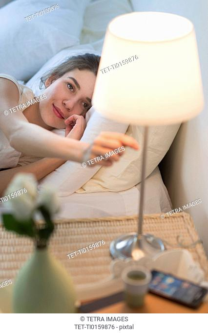 Woman turning off lamp