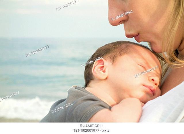 Mother holding newborn daughter on beach