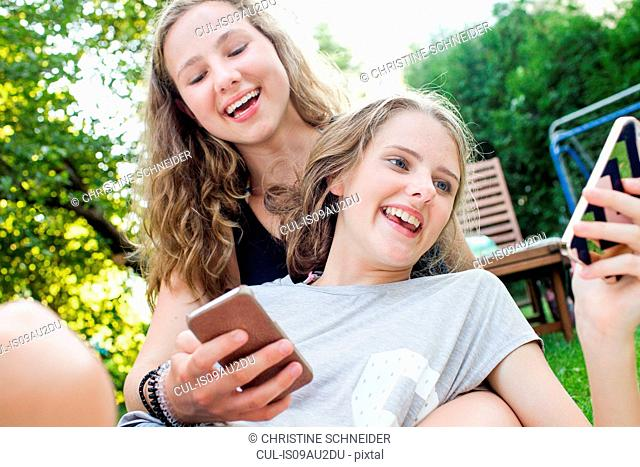 Two teenage girls reading smartphone texts in garden