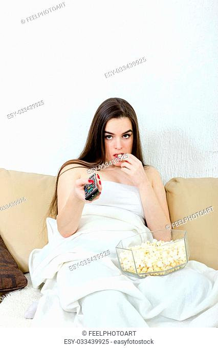 Lonely bored pretty cute young girl sitting on the couch at home and the list of programs on TV with the remote while eating popcorn
