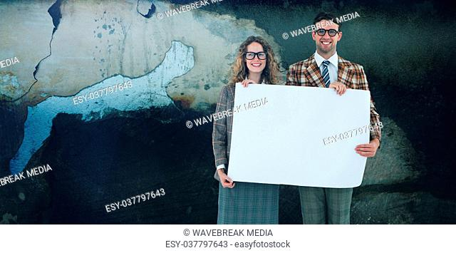 Composite image of geeky hipster couple holding poster
