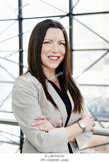 Portrait of a mature business woman in the atrium of an office building; Edmonton, Alberta, Canada